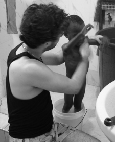bathing child with fevers from malaria in Africa